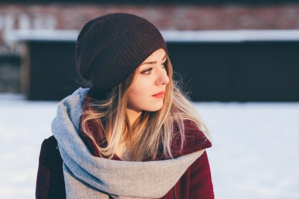 Devojka sa crnom kapom na belom snegu